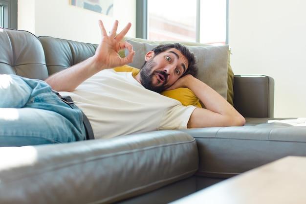 Junger bärtiger mann ruht auf einer couch