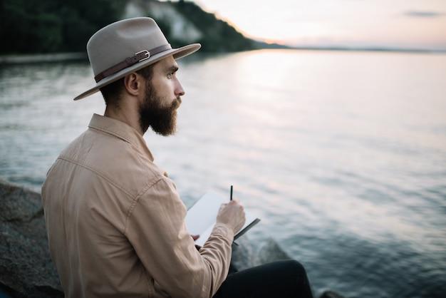 Junger bärtiger mann schreibt notizen in ein notizbuch und genießt schönen sonnenuntergang. zeit zu reisen konzept