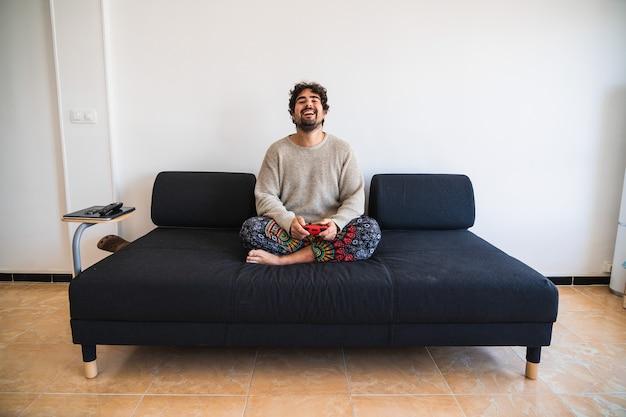 Junger bärtiger mann sitzt auf einer couch, die konsole spielt