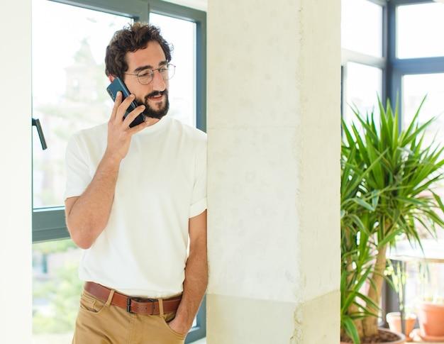 Junger bärtiger mann zu hause. mit einem smartphone