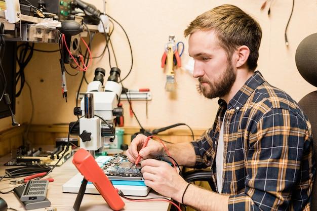 Junger bärtiger mechaniker mit zwei lötkolben, die am arbeitsplatz in der werkstatt sitzen, während gebrochenes gerät repariert wird