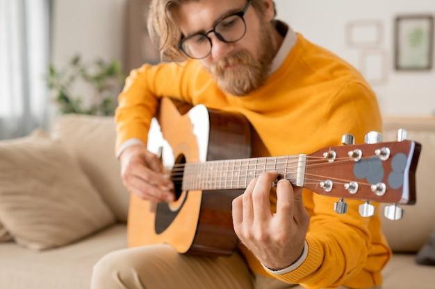 Junger bärtiger musiklehrer, der etwas erklärt oder frage des online-publikums während des unterrichts in der häuslichen umgebung beantwortet