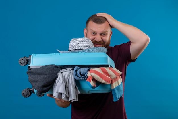 Junger bärtiger reisender mann, der koffer voll von kleidern hält, die verwirrt und sehr ängstlich mit der hand auf seinem kopf aussehen