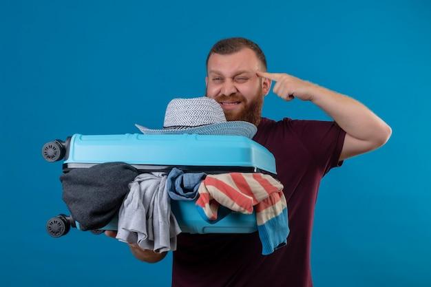 Junger bärtiger reisender mann, der koffer voller kleidung hält, der seine schläfe zeigt, die versucht, sich zu erinnern