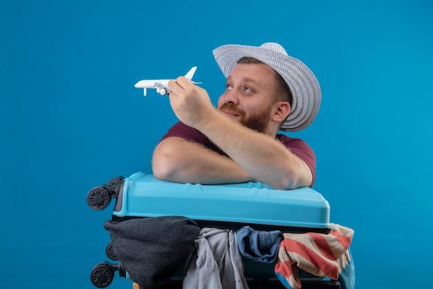 Junger bärtiger reisender mann im sommerhut mit koffer voll von kleidern, die spielzeugflugzeug spielerisch optimistisch und glücklich lächelnd beiseite mit verträumtem blick 2 schauen