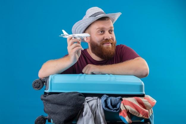Junger bärtiger reisender mann im sommerhut mit koffer voll von kleidern, die spielzeugflugzeug verspielt optimistisch und glücklich lächelnd beiseite mit verträumtem blick schauend halten