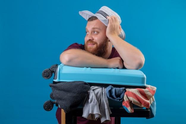 Junger bärtiger reisender mann im sommerhut mit koffer voller kleidung optimistisch und glücklich lächelnd beiseite mit verträumtem blick schauend