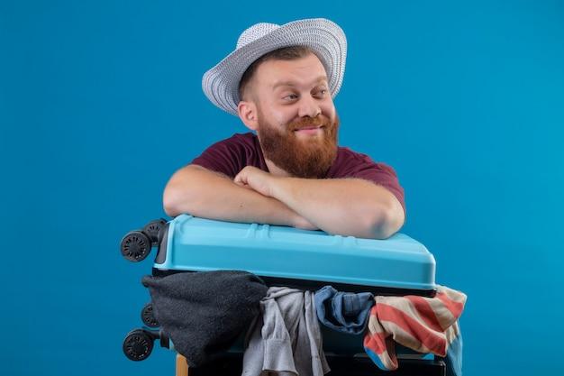 Junger bärtiger reisender mann im sommerhut mit koffer voller kleidung optimistisch und glücklich lächelnd beiseite schauend