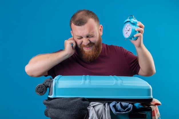 Junger bärtiger reisender mann mit koffer voller kleidung, der wecker hält, der sein ohr mit finger mit genervtem ausdruck bedeckt