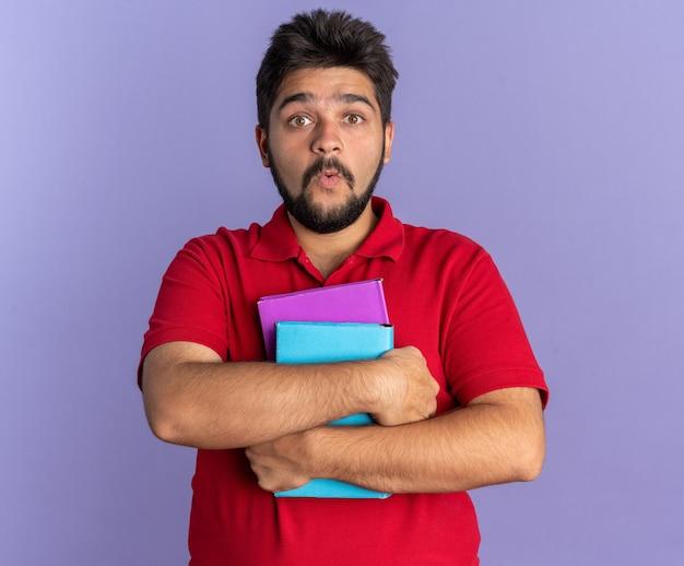 Junger bärtiger student im roten polohemd, der bücher hält, die erstaunt und überrascht aussehen