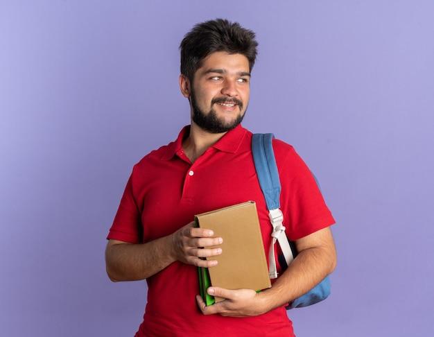 Junger bärtiger student im roten poloshirt mit rucksack, der bücher hält, die mit einem lächeln auf einem glücklichen gesicht beiseite schauen