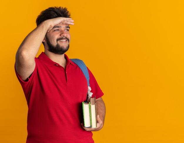 Junger bärtiger student im roten poloshirt mit rucksack, der bücher hält, die weit weg schauen, mit der hand auf dem kopf, die fröhlich stehend lächelt