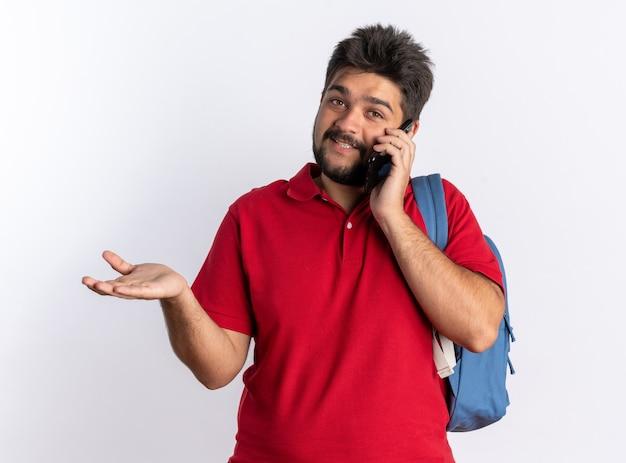 Junger bärtiger student im roten poloshirt mit rucksack, der fröhlich lächelt, während er auf dem handy über der weißen wand spricht