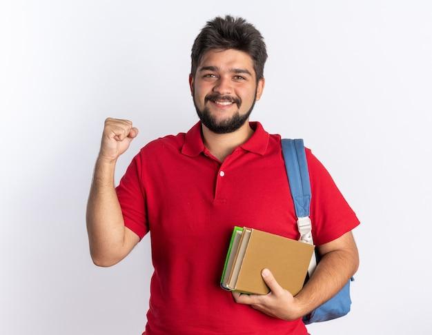 Junger bärtiger student im roten poloshirt mit rucksack, der notizbücher hält, sieht glücklich und aufgeregt aus, die faust über der weißen wand stehend?