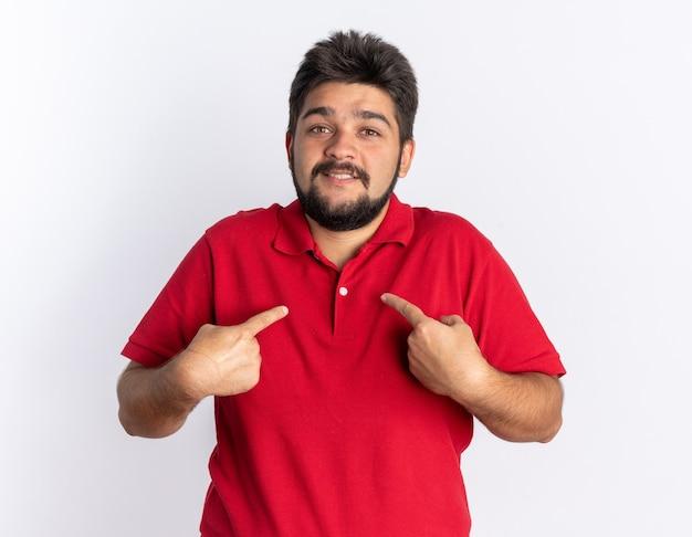 Junger bärtiger student im roten poloshirt sieht glücklich und überrascht aus und zeigt mit zeigefingern auf sich selbst stehend