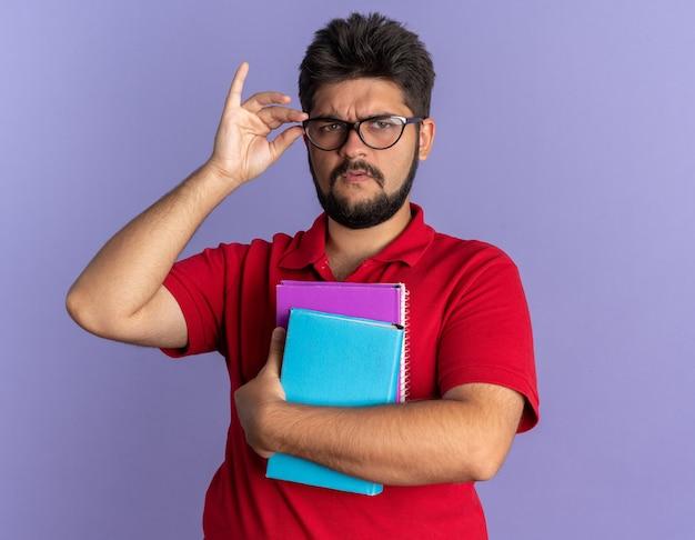 Junger bärtiger student in rotem polohemd, der bücher hält, die eine brille tragen, mit ernstem gesicht, das über blauer wand steht?