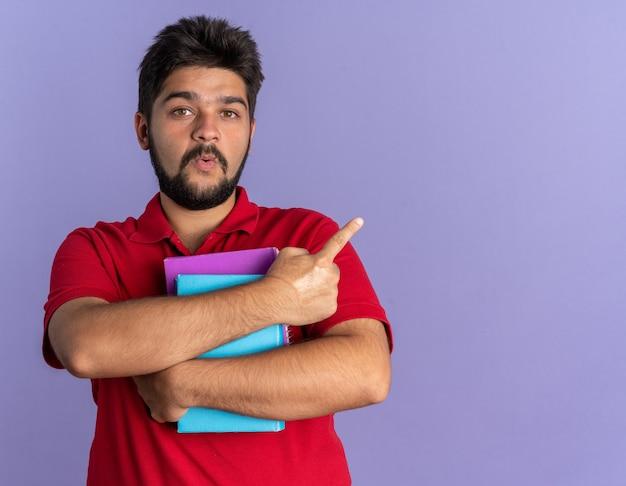 Junger bärtiger student in rotem polohemd, der bücher hält und überrascht aussieht und mit dem zeigefinger auf die seite zeigt