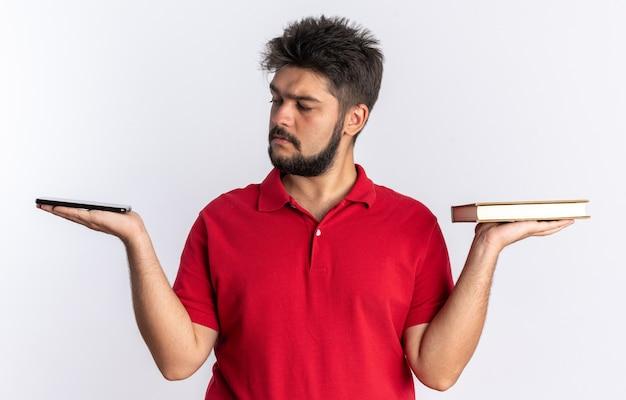 Junger bärtiger student in rotem polohemd, der notizbücher in den händen hält und sie mit ernstem gesicht betrachtet