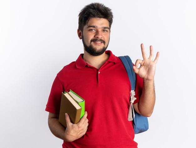 Junger bärtiger student in rotem polohemd mit rucksack, der notebooks hält und lächelt, die ein ok-zeichen über der weißen wand zeigt