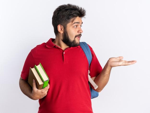 Junger bärtiger student in rotem polohemd mit rucksack, der notizbücher hält, die überrascht beiseite schauen und mit dem arm seiner hand kopienraum über der weißen wand präsentieren?