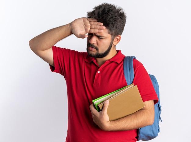 Junger bärtiger student in rotem polohemd mit rucksack, der notizbücher hält, die unwohl aussehen und die hand auf der stirn halten und fieber haben