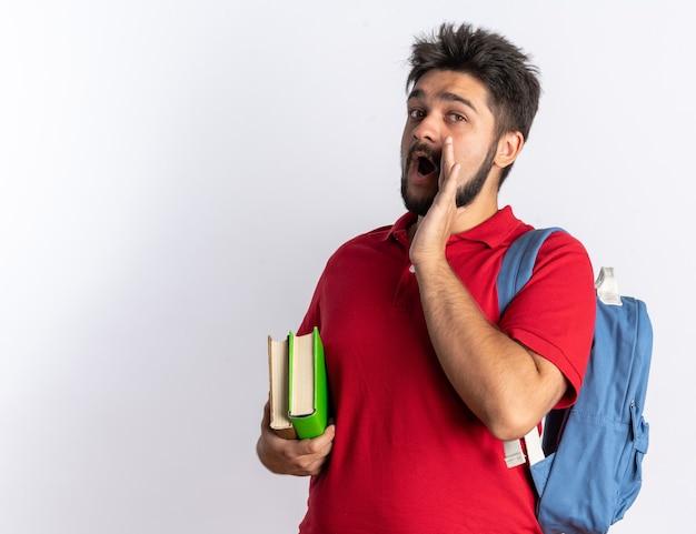 Junger bärtiger student in rotem poloshirt mit rucksack, der notizbücher hält, die jemanden mit der hand auf dem mund stehend anrufen