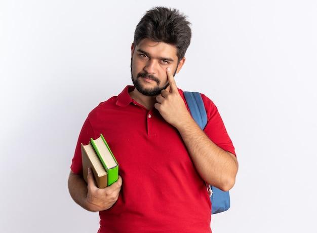 Junger bärtiger student in rotem poloshirt mit rucksack, der notizbücher hält, die mit dem finger auf sein auge zeigen, das über weißer wand steht?