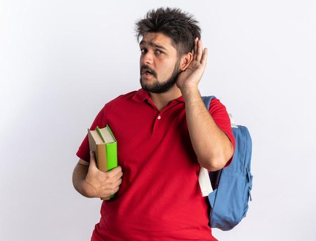 Junger bärtiger student in rotem poloshirt mit rucksack, der notizbücher hält und versucht, mit der hand am ohr zuzuhören