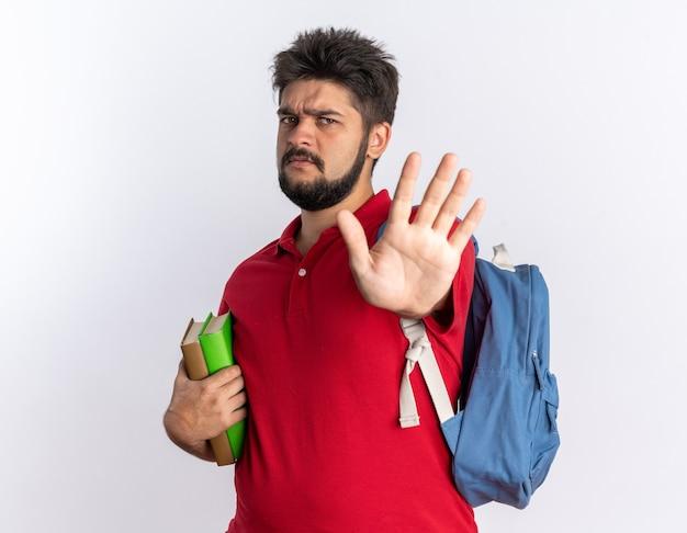 Junger bärtiger student in rotem poloshirt mit rucksack, der notizbücher mit stirnrunzelndem gesicht hält und stoppgeste mit der hand über der weißen wand macht
