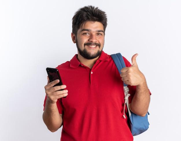 Junger bärtiger student in rotem poloshirt mit rucksack, der smartphone hält und fröhlich lächelt und daumen nach oben über weißer wand zeigt
