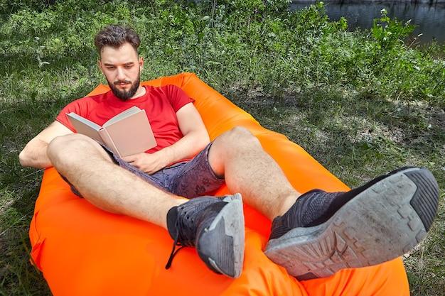Junger bärtiger student liest buch, das auf orangeem luftsofa auf gras im wald während des ökotourismus liegt.