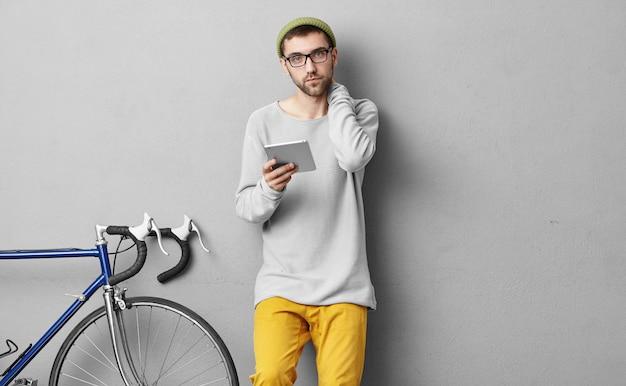 Junger bärtiger tourist, der moderne tafel in der hand hält und nach route sucht, wohin zu gehen und was als nächstes mit seinem fahrrad zu erkunden ist. stilvoller typ, der zu hause ein modernes gerät verwendet, bevor er sein fahrrad fährt