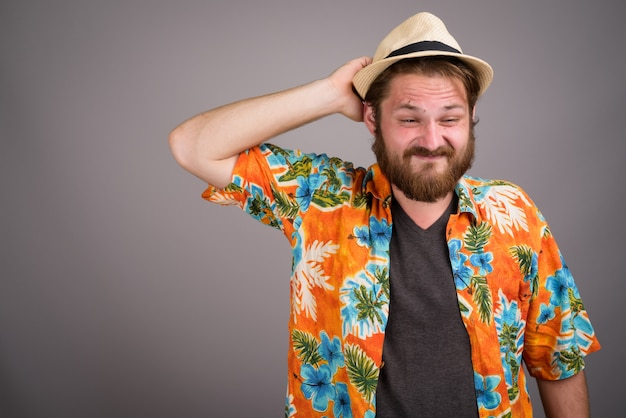 Junger bärtiger touristenmann bereit für urlaub gegen graues backgr
