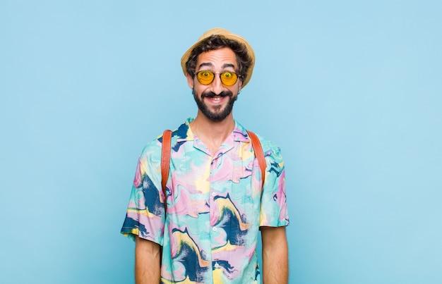 Junger bärtiger touristenmann, der glücklich und doof mit einem breiten, lustigen, verrückten lächeln und weit geöffneten augen schaut