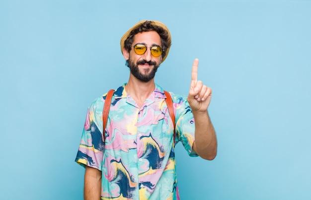 Junger bärtiger touristenmann, der lächelt und freundlich schaut, nummer eins oder zuerst mit der hand vorwärts zeigend, herunterzählend