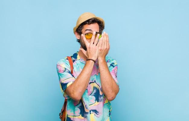 Junger bärtiger touristenmann, der sich ängstlich oder verlegen fühlt und mit halb mit händen bedeckten augen späht oder spioniert