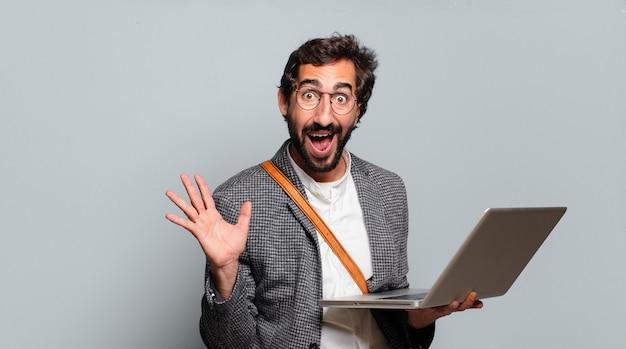 Junger bärtiger und verrückter geschäftsmann mit einem laptop