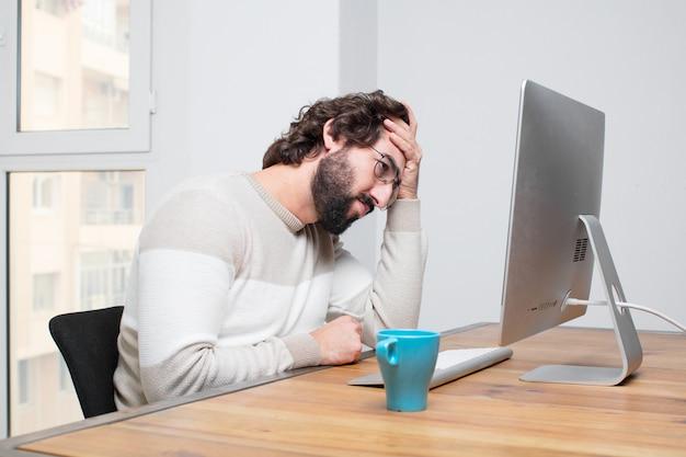 Junger bärtiger verrückter freiberufler, der mit seinem computer arbeitet
