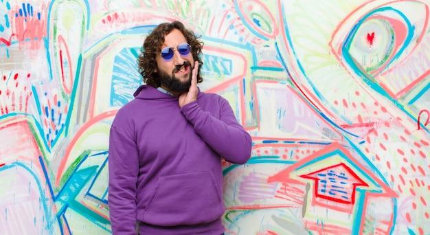 Junger bärtiger verrückter mann, der backe hält und schmerzliche zahnschmerzen erleidet, krank, elend und unglücklich sich fühlt und nach einem zahnarzt gegen graffitiwand sucht