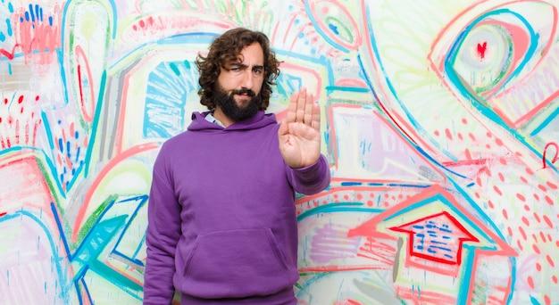 Junger bärtiger verrückter mann, der die offene palme der ernsten, strengen, missfallenen und verärgerten vertretung macht endgeste auf graffitiwand schaut