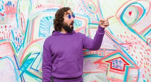 Junger bärtiger verrückter mann, der entsetzt und überrascht sich fühlt, in ehrfurcht mit erstauntem blick mit offenem mund gegen graffiti zeigt und nach oben schaut