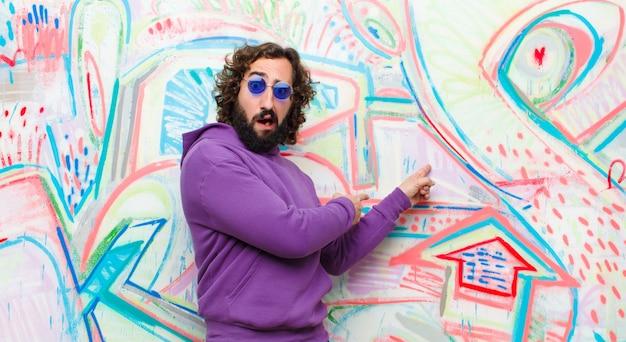 Junger bärtiger verrückter mann, der entsetzt und überrascht sich fühlt und auf copyspace auf der seite mit überraschtem, mit offenem mund blick gegen graffiti zeigt