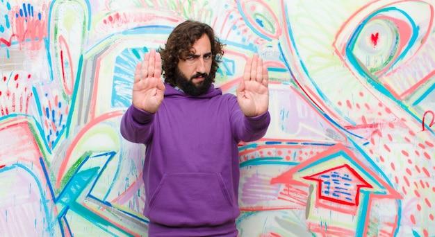 Junger bärtiger verrückter mann, der ernsten, unglücklichen, verärgerten und missfallenen verbietenden eintritt schaut oder halt mit beiden offenen palmen auf graffitiwand sagt