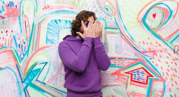 Junger bärtiger verrückter mann, der erschrocken oder verlegen sich fühlt, mit den augen späht oder ausspioniert, die mit den händen gegen graffitiwand halb bedeckt sind