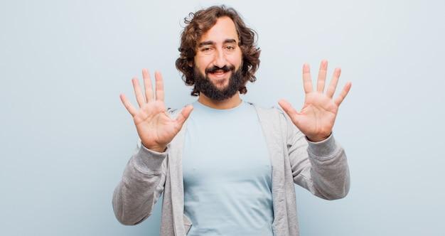 Junger bärtiger verrückter mann, der freundlich lächelt und schaut und nr. zehn oder zehntel mit der hand vorwärts zeigt und unten gegen flache farbe zählt