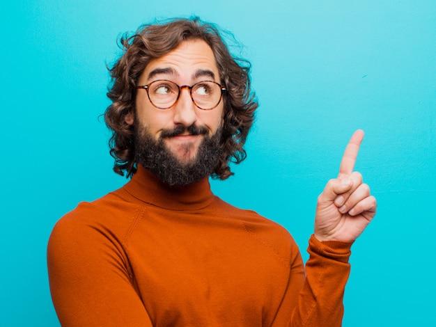 Junger bärtiger verrückter mann, der glücklich lächelt und seitlich schaut, sich wundert, eine idee gegen flache farbe denkt oder hat