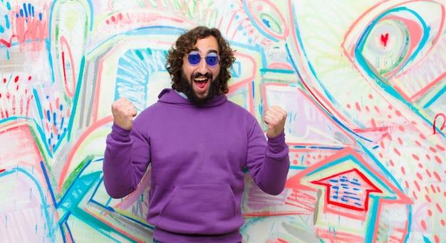 Junger bärtiger verrückter mann, der glücklich, positiv und erfolgreich sich fühlt und sieg, leistungen oder viel glück gegen graffitiwand feiert