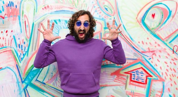Junger bärtiger verrückter mann, der in der panik oder in der wut, entsetzt, erschrocken oder wütend, mit den händen nahe bei kopf auf graffitiwand schreit