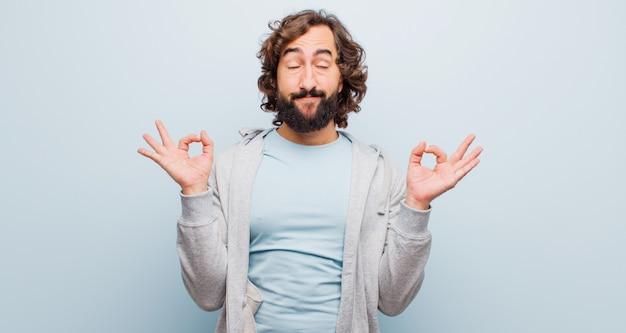 Junger bärtiger verrückter mann, der konzentriert und meditierend schaut, zufrieden und entspannt sich fühlt, eine wahl denkt oder trifft