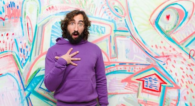 Junger bärtiger verrückter mann, der sich schockiert, erstaunt und überrascht fühlt, mit der hand auf der brust und offenem mund und sagt, wer, ich? gegen graffiti